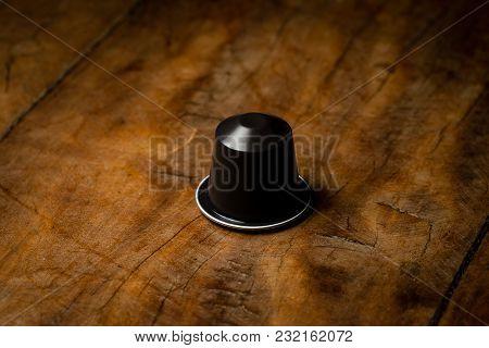 Coffee Pod On Wooden Table, Hero Shot, Hard Light, Focused Lighting, Brown Pod.