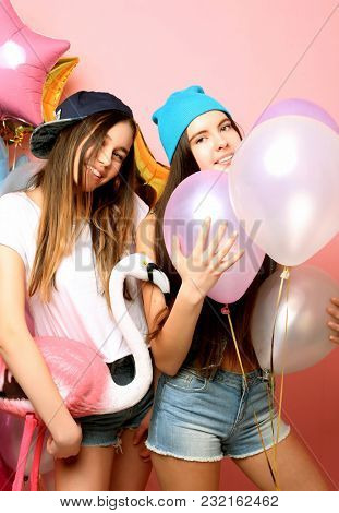 Two funny friends make grimace and have fun . Two emotional girls hold balloons and posing against pink wall.