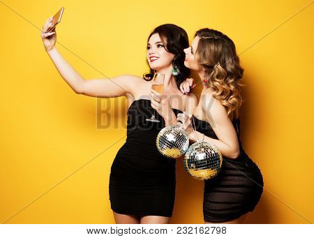 lifestyle and people concept: two beautiful   women with wine glasses and disco ball, party time