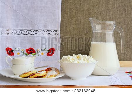 Still Life Of Dairy Products On A Background Of A Towel With Embroidery   Of Red Poppies. Cheesecake