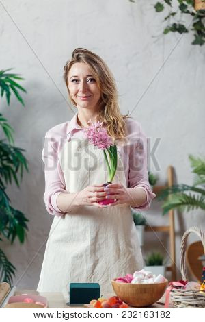 Portrait of florist woman in apron at room with flowers