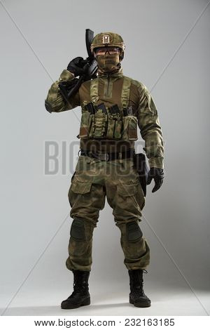 Photo of soldier in camouflage with gun in studio
