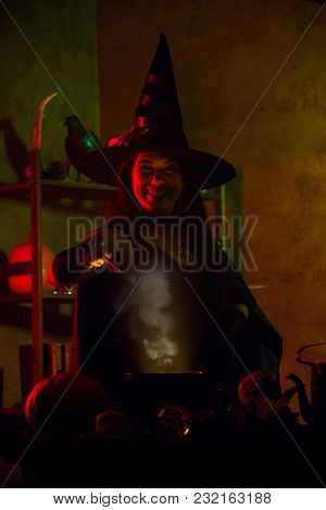 Dark photo of young witch in black hat with outstretched hand with magic wand and cauldron
