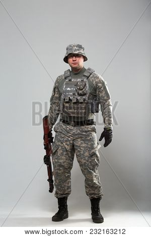 Full-length picture of military man in helmet with gun