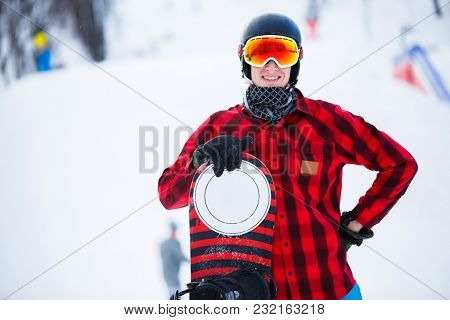 Image of standing athlete with snowboard in winter park
