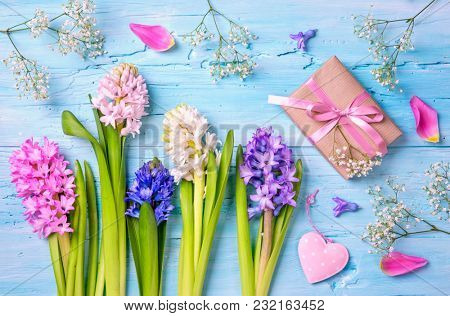 Pastel colored flowers and a gift box on a blue background