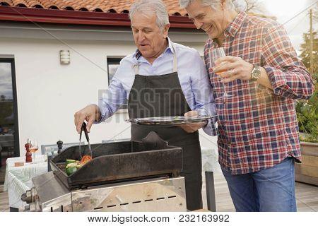 Senior friends having fun preparing grilled meal at home