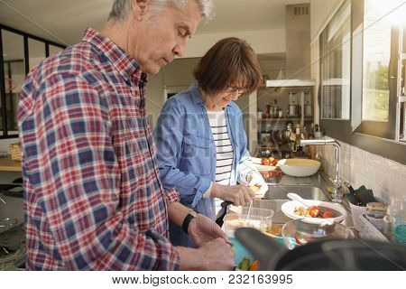 Happy senior couple at home preparing fruit salad