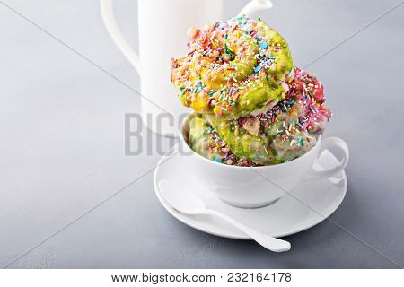 Unicorn Donuts With Colorful Glaze And Sprinkles In A White Cup