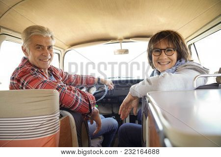 Cheerful senior couple sitting in van during road trip
