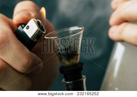 A Man Smokes Cannabis Weed, Bong Lighter In His Hands. Smoke On A Black Background. Concepts Of Medi