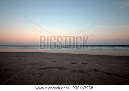 Footprints In The Sand On The Beach Along The Coast Shoreline After Sunset In The Evening