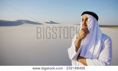 Confident Muslim Arabian Uae Sheikh With Serious Face Puts Hand To Chin And Reflects On Future Plans