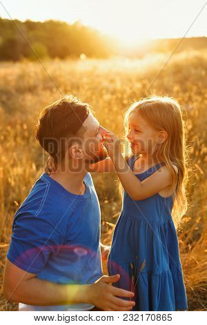 Family Time. Father And Daughter On The Meadow At Sunset. The Little Girl Is Holding Her Father By T