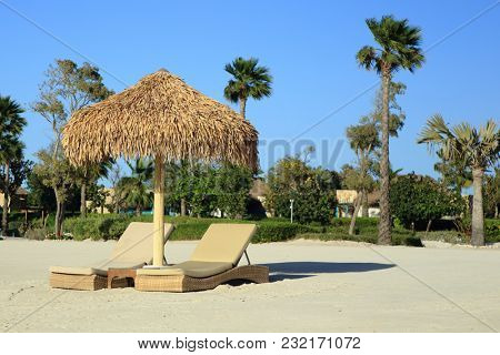 DOHA, Qatar - March 14, 2018: Beach chairs and umbrellas waiting for visitors at Qatar's luxury Banana Island resort