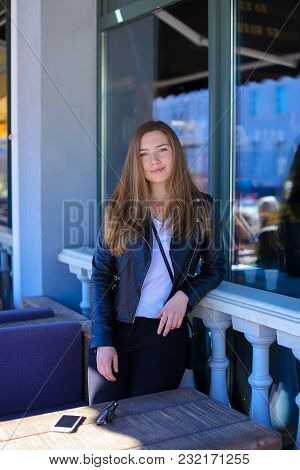 Gladden Female Person Standing Near Window Of Street Cafe And Sofa. Concept Of Resting Outside.