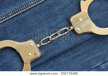 Police Steel Handcuffs Lying On Dark Blue Jeans Background