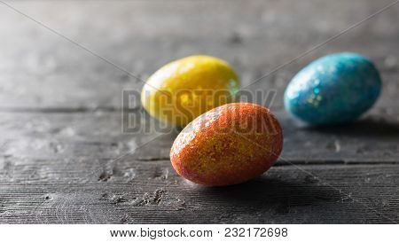 Three Colorful Eggs On A Dark Wooden Table. The Decoration Of The Easter Table. Great Christian Holi