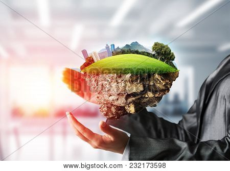 Business Woman In Suit Keeping Green Island With Landscape And City In Her Hands With Sunlight And O