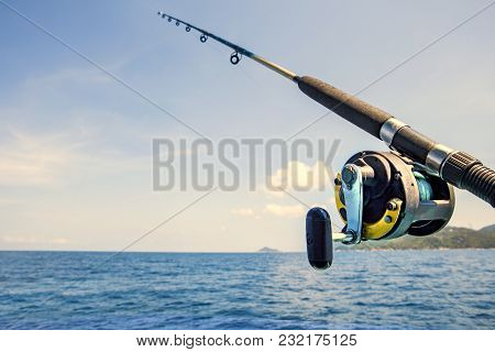 Old Fishing Rod And Blue Sea Water