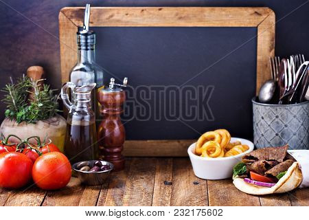 Greek Food Background With Gyro Pita, Curly Fries And Chalkboard Copy Space
