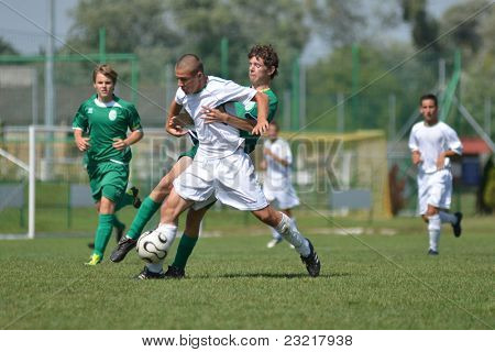 KAPOSVAR, HUNGARY - SEPTEMBER 5: Attila Kovacs (white 11) in action at the Hungarian National Championship under 17 game Kaposvar (white) vs. Nagyatad (green) September 5, 2011 in Kaposvar, Hungary.