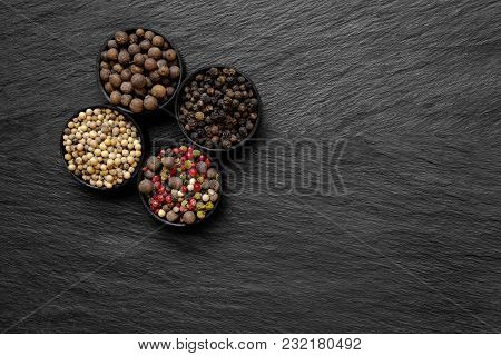 Black, Green, Pink, White And Fragrant Pepper Grains In Round Jars Placed On Black Stone Surface Bac