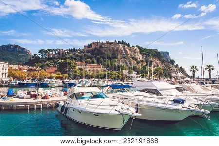 Low Angle View On Chateau De Cassis Castle On Top Of Hill And Close Up Of Boats Moored In Harbour On