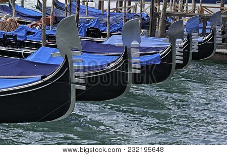 Detail On The Steel Prow Of A Venetian Gondola Moored In The Canal In Front Of San Marco Square In V