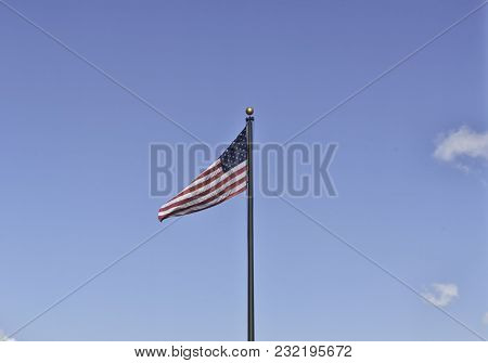 An American Flag On A Black Metal Pole Weaving In The Clear Sky On The 4th Of July. Stars And Stripe