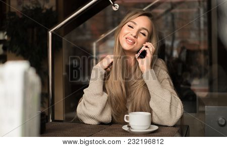Young Happy Woman Talking On Mobile Phone With Friend While Sitting Alone In Modern Coffee Shop Inte