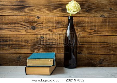 A White Rose In A Bottle And A Books On Wooden Background