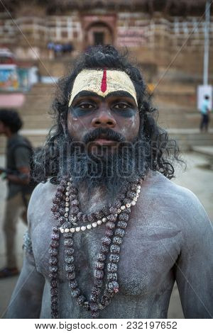 VARANASI, INDIA - MAR 17, 2018: Sadhu (holy man) on the ghats of Ganga river. Varanasi is most important pilgrimage sites in India, one of the 7 sacred cities of Hinduism.