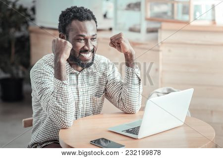 My Success. Nice Cheerful Handsome Man Looking At The Laptop Screen And Expressing His Happiness Whi