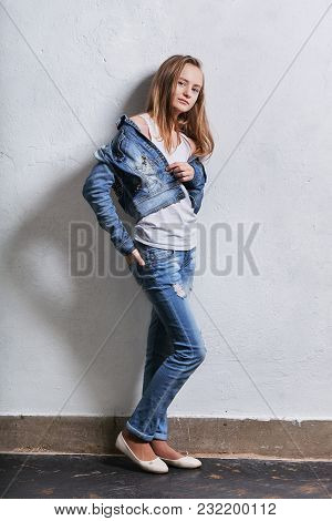 Fashion Teenager Girl Standing Leaning Back Against A White Concrete Wall. Young Caucasian Woman 11-