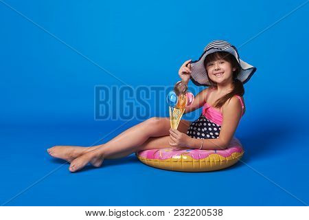 Pretty Little Girl Swimsuit, Beach Hat Sitting On Inflatable Ring Relaxation Summertime. Fashionable