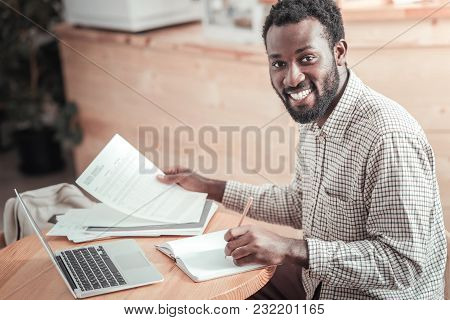 University Exams. Nice Joyful Positive Man Sitting At The Table And Looking At You While Finals
