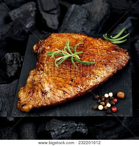 Juicy Roasted Steak With Aromatic Spices On A Black Slide