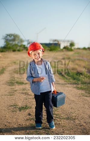 Happy Smiling Little Boy In Helmet With Case Of Tools Goes To Work
