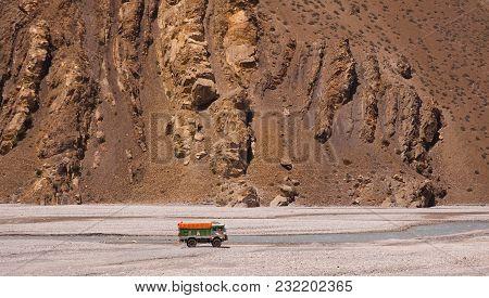 Truck Full Of Stuff Driving In Watercourse In Low Water Season. Huge Textured Brown Rocks Background