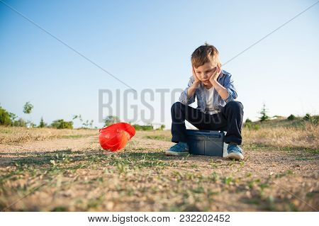Sad Little Kid Sitting On Box With Tools And Helmet Lying Next To Him Losing Job