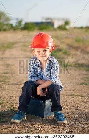 Cute American Caucasian Kid Wearing Orange Helmet Sits On Box With Tools After Hard Working Day In S