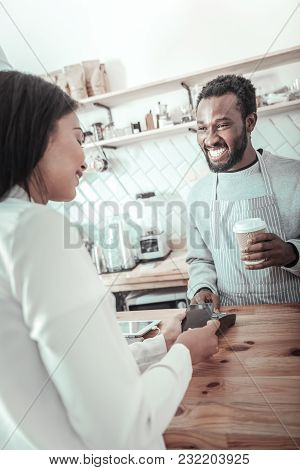 Friendly Barista. Cheerful Positive Delighted Man Smiling And Talking To The Customer While Giving H