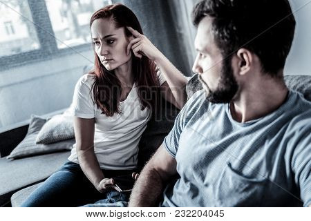 Bed Relationships. Redhead Serious Deep Woman Sitting On The Sofa Near Her Husband Holding The Cellp