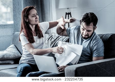 Its Because Of You. Stressful Young Worried Woman Sitting On The Sofa Holding Papers And Quarreling