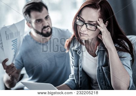 Im Tired Of It. Exhausted Upset Bespectacled Woman Sitting Near Quarrelsome Man Holding Hand Near He