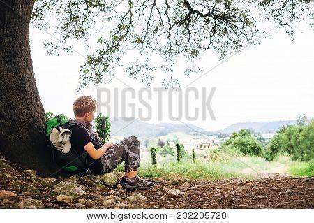 Little Backpacker Traveler Rest Under Tree On Country Road