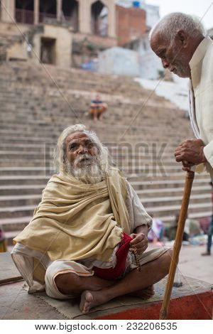VARANASI, INDIA - MAR 15, 2018: Sadhu (holy man) on Dashashwamedh Ghat is the main and probably oldest ghat of Varanasi located on the Ganges, close to Kashi Vishwanath Temple.