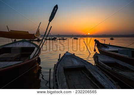 VARANASI, INDIA - MAR 18, 2018: Dawn on the Ganges river, with the silhouettes of boats with pilgrims. According to legends, the city was founded by God Shiva about 5000 years ago.