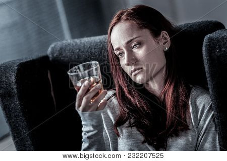 I Need To Drink. Upset Redhead Frustrated Woman Sitting In The Dark Room Feeling Bad Herself And Loo